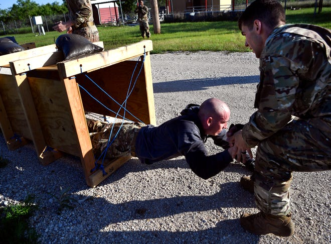 Lane Renner pulls Andrew Lehman out of a crawling box as the technical sergeants ran an obstacle course Wednesday at Dyess Air Force Base. The men are military police officers, the course and other activities this week were in conjunction with National Police Week, which honors law enforcement officers.