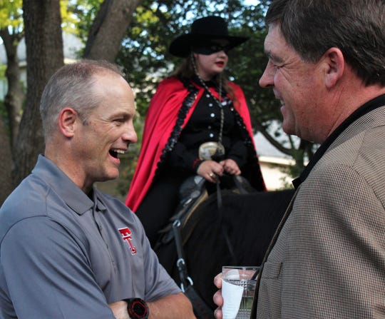 New Texas Tech football coach Matt Wells, left, shares a laugh with Steve Senter at Tuesday's gathering of Abilene Red Raiders Nation at the home of Scott Dueser. In the background is the Masked  Rider, making sure no Longhorns or Aggies sneaked in. May 14, 2019