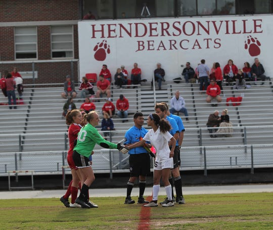 Warlassies captain Brooklynn Roland shakes hands with players from Hendersonville at midfield on May 15, before Owen was eliminated in the third round of the NCHSAA state playoffs.