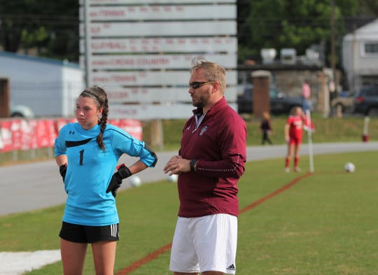 Owen soccer head coach David Fiest meets with senior C.J. Graham before the Warlassies take the field against Hendersonville on May 15.