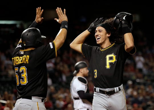 Pittsburgh Pirates shortstop Cole Tucker celebrates his two-run home run with Melky Cabrera (53) during the eighth inning of the team's baseball game against the Arizona Diamondbacks, Tuesday, May 14, 2019, in Phoenix.