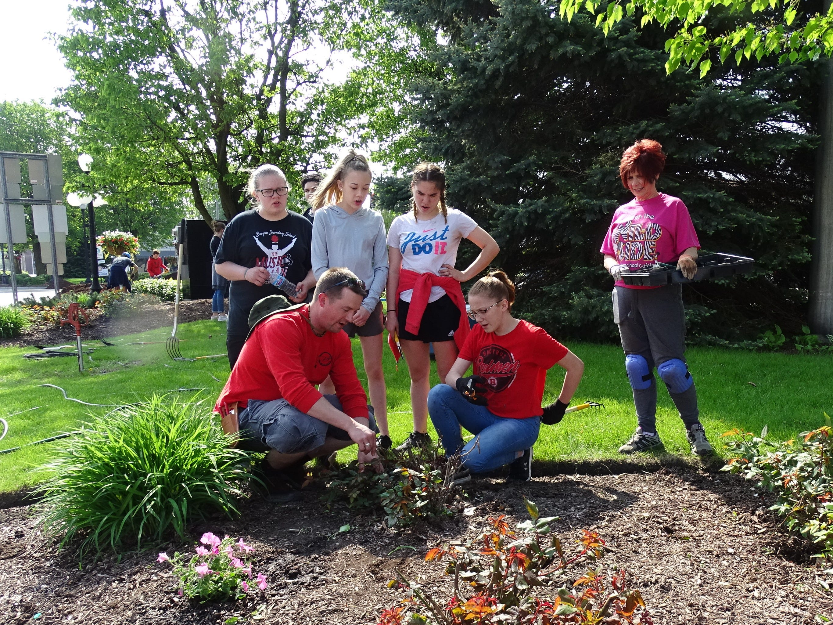 Bucyrus teacher Scott Mental, front left, discusses the proper way to prune bushes while Shirley Chapman of the Earth, Wind and Flowers Garden Club, right, watches.