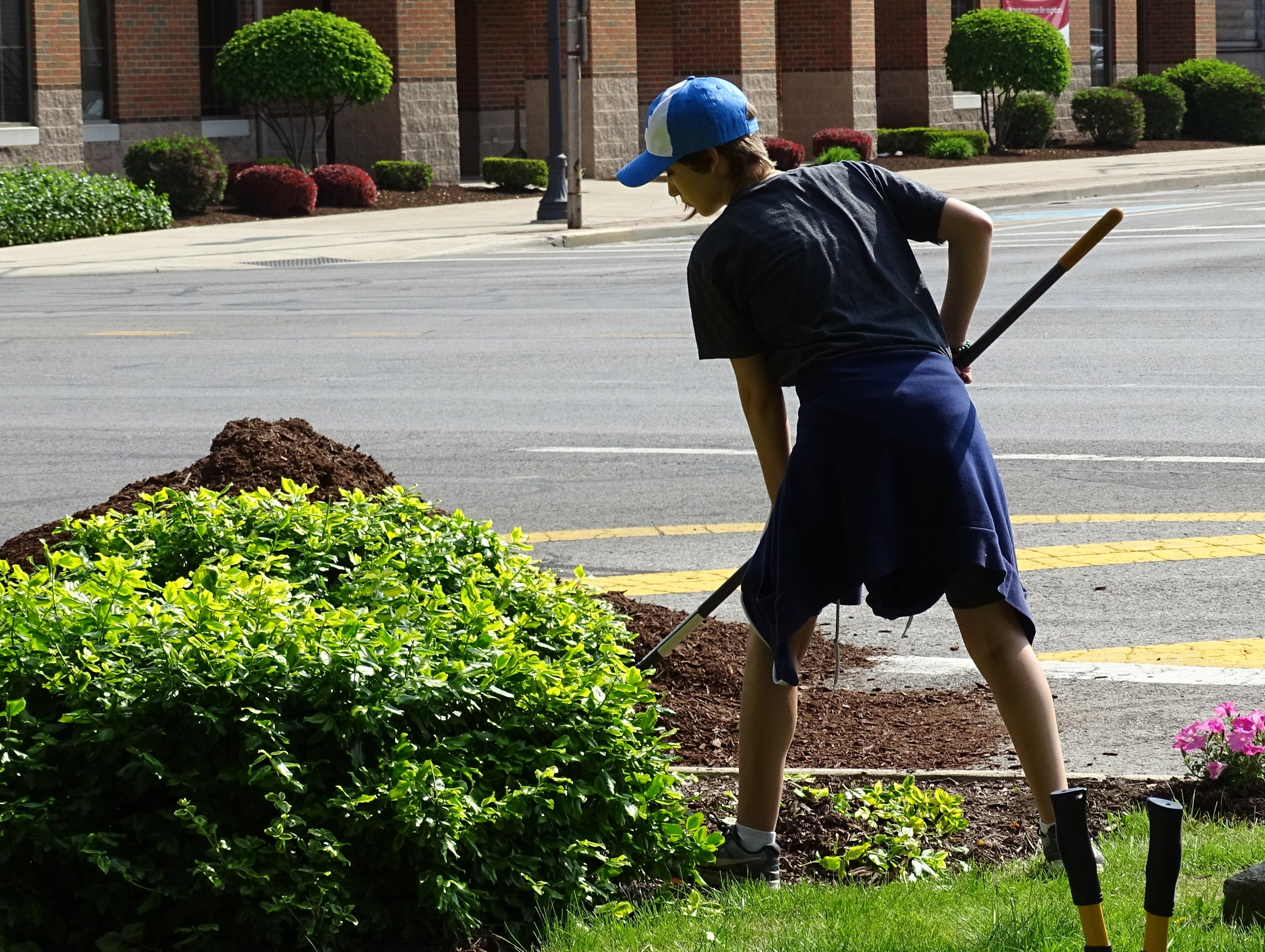 Parker Boggs, a Bucyrus Middle School seventh-grader, rakes clippings at Washington Square in downtown Bucyrus on Thursday morning.