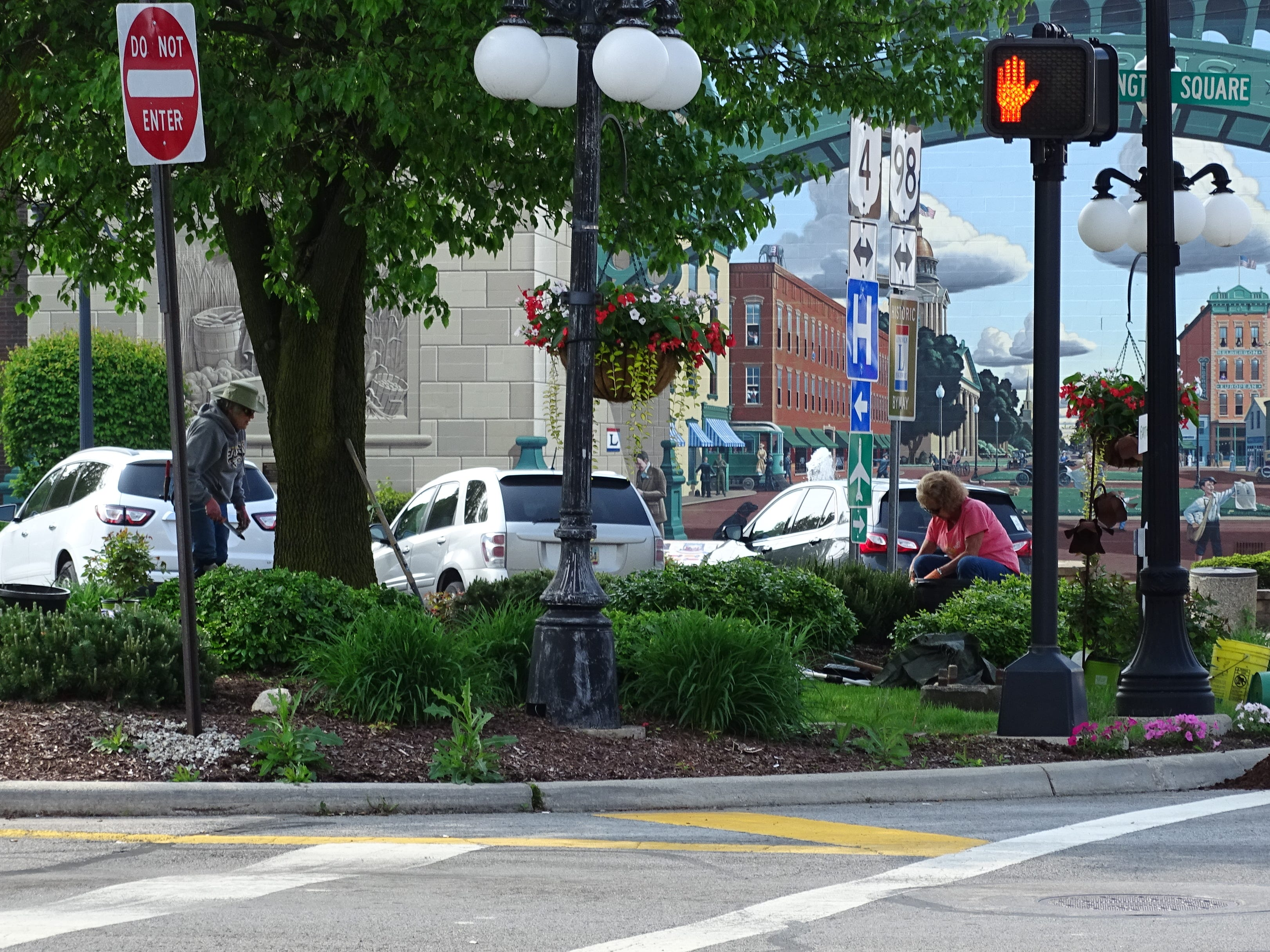 Earth, Wind and Flowers Garden Club members clean up the landscaping at Washington Square in downtown Bucyrus on Thursday morning.