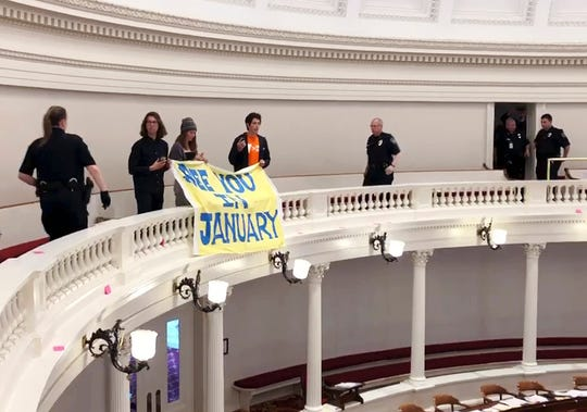 Police approach three people holding a banner, Thursday, May 16, 2019, in the visitors' gallery of the Vermont House of Representatives in Montpelier, Vt. While the House was in session, several protesters began to shout climate slogans and throw leaflets onto the floor from the gallery. After most protesters had departed, the three remained and were arrested after they refused repeated orders from capital police to leave.