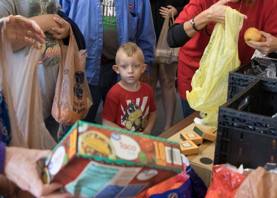 A young boy picks out some taco shells as he and his mom receive food at a food pantry in Ohio.
