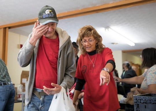 Chillicothe resident Steve, left, cries tears of joy as he receives food from the Zion Baptist Church food pantry with the help of Karen Nutter, who also prays with him, on May 14, 2019, in Chillicothe, Ohio. The food pantry was started over 40 years ago to help those in need and will continue every second and fourth Tuesday of the month from 10 a.m. to 12 p.m.