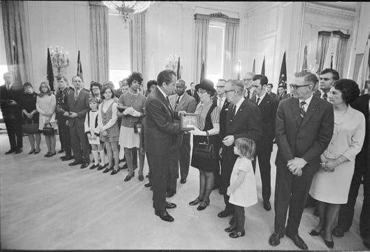 President Richard Nixon hands the framed Medal of Honor awarded posthumously to Sgt. Charles Clinton Fleek for his sacrifice in Vietnam to Fleek's mother Catherine Feb. 16, 1971 at the Whitehouse. Catherine's son Sonny is behind and between her husband and Charles' father Wilford. Charle's younger sister Carla is the little girl.