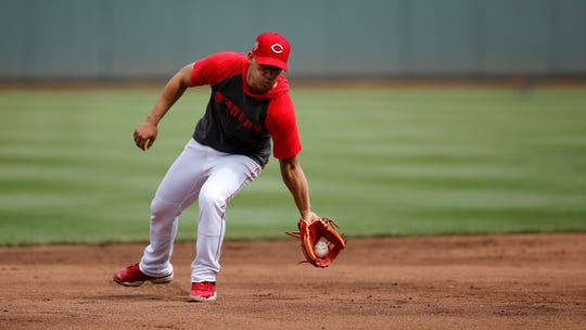 Cincinnati Reds shortstop Jose Iglesias (4) practices special fielding moves during batting practice before the MLB National League game between the Cincinnati Reds and the Chicago Cubs at Great American Ball Park in downtown Cincinnati on Wednesday, May 15, 2019.