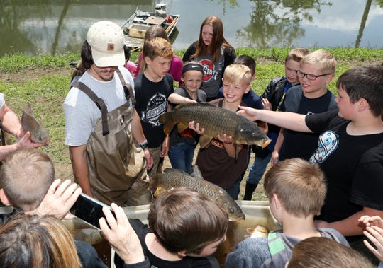 Students from Warsaw Elementary School get up close and personal with fish from the Muskingum River during AEP Conesville's outdoor educational event.
