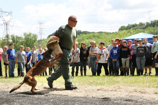 Coshocton County Sheriff's Office Deputy Steven Mox puts on a demonstration with his K9 partner Chili during AEP Conesville's  outdoor educational event Wednesday. Watching are students from Ridgewood Elementary School.