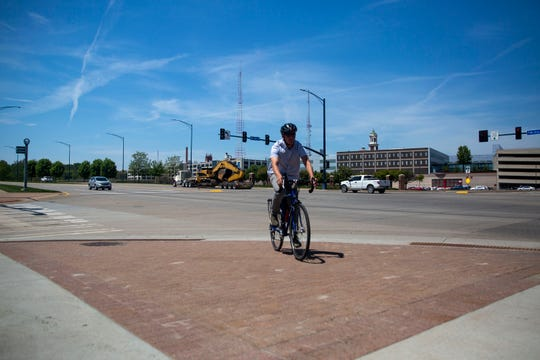 Jeremy Lewis, director of the Street Collective, demonstrates the awkward angle bikers had to take before the city of Des Moines redesigned a downtown curb and crosswalk after a series of bike accidents there.