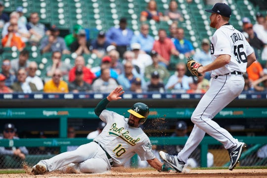 Athletics shortstop Marcus Semien slides safely into home plate on a wild pitch by Tigers pitcher Spencer Turnbull in the third inning on Thursday, May 16, 2019, at Comerica Park.
