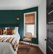 A bold green hue in the master bedroom was inspired by a wool fabric that covers the headboard.