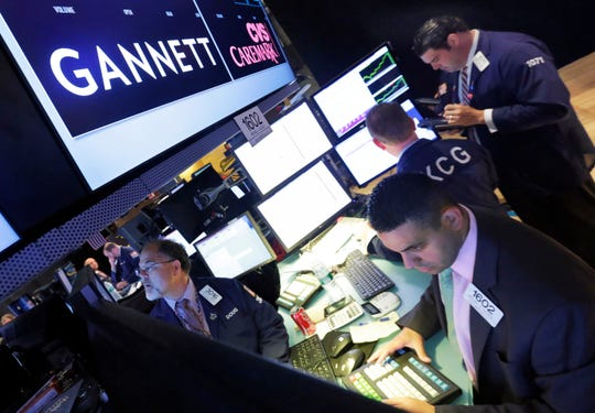 In this Aug. 5, 2014, file photo, specialist Michael Cacace, foreground right, works at the post that handles Gannett, on the floor of the New York Stock Exchange.