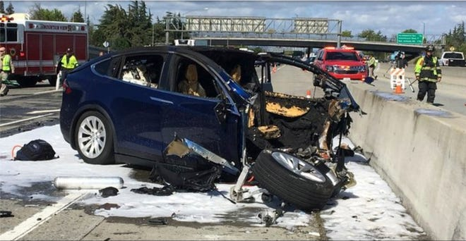 In this Friday March 23, 2018 photo provided by KTVU, emergency personnel work a the scene where a Tesla electric SUV crashed into a barrier on U.S. Highway 101 in Mountain View, Calif. The NTSB has sent investigators to look into the fatal crash and fire.