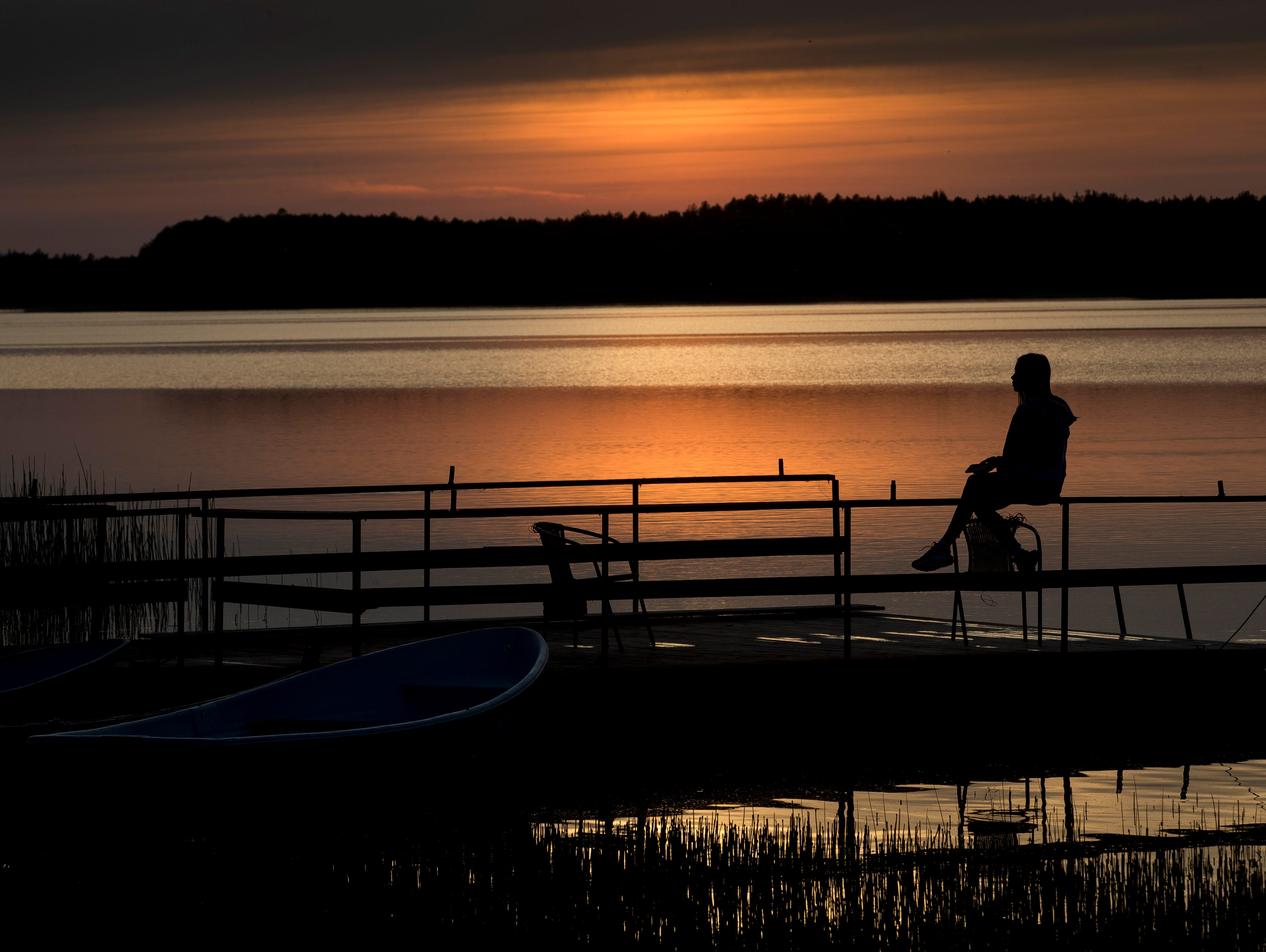 A girl is silhouetted by the sunset on a lake near the small town of Ignalina, some 75 miles north of the capital Vilnius, Lithuania, on Wednesday, May 15, 2019.