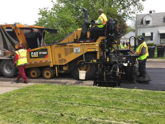 Workers repave Marseilles in the eastside Cornerstone Village neighborhood on Thursday.