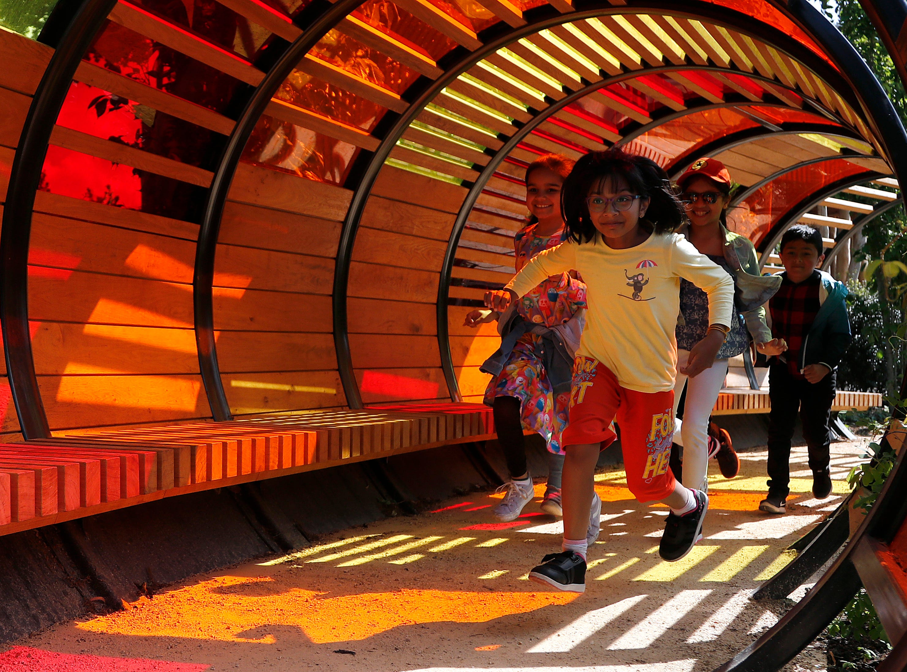 Children enjoy the light tunnel at the new Children's Garden at Kew, designed around the elements that plants need to grow, at Kew Gardens in London, Thursday, May 16, 2019. The new garden covers the equivalent of nearly 40 tennis courts, and is for youngsters to explore and play in.