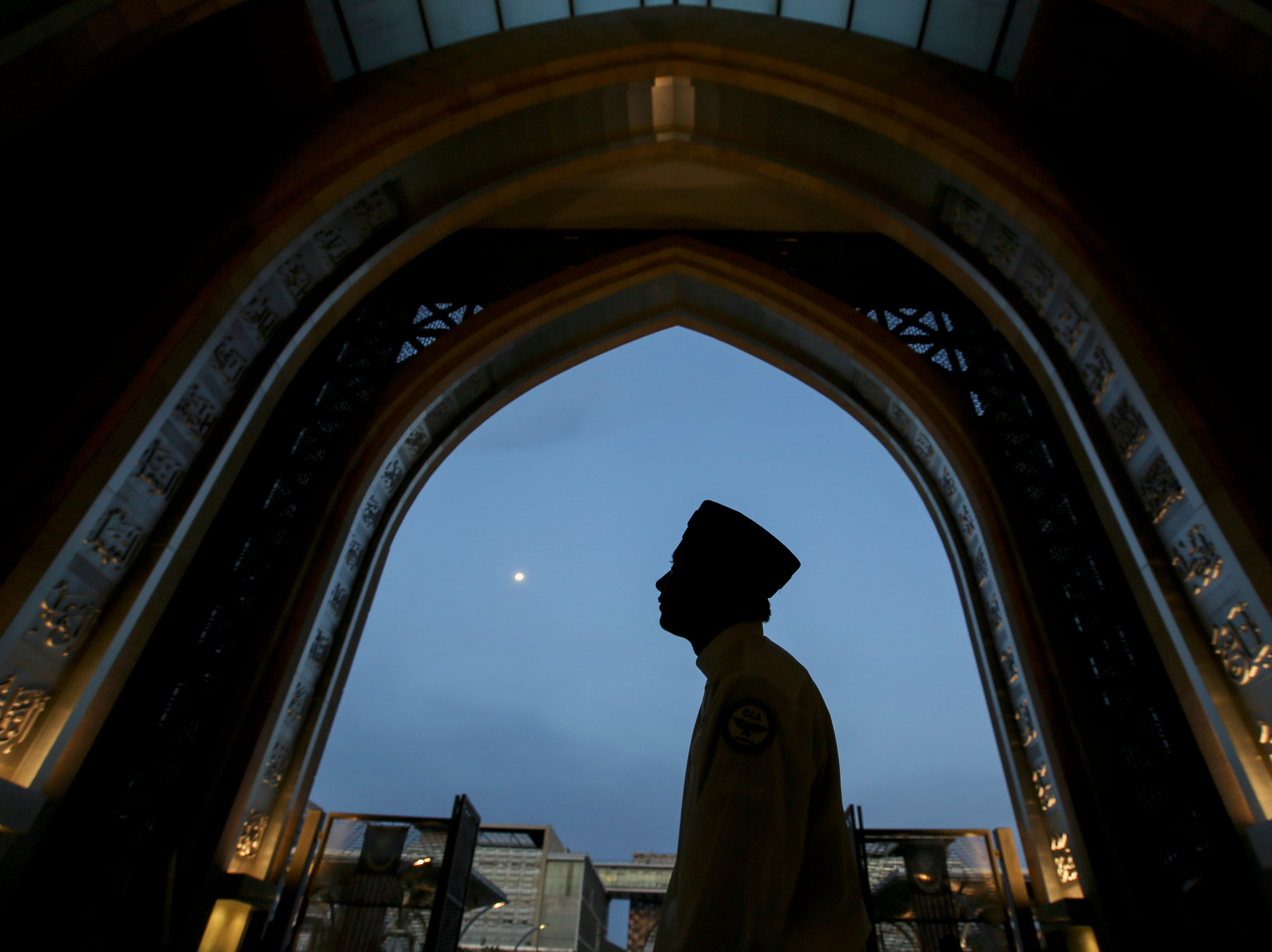 A silhouette of a Muslim man arrives at a mosque for Iftar during the holy Islamic month of Ramadan in Kuala Lumpur, Malaysia, Thursday, May 16, 2019.