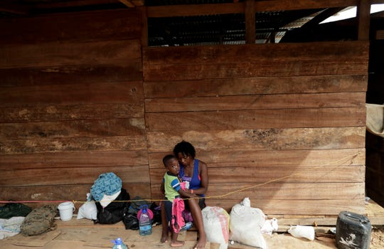 In this May 10, 2019 photo, a migrant woman and her son rest under a wooden house in Darien Province, Panama.