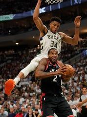 Toronto Raptors' Kawhi Leonard tries to shoot in front of Milwaukee Bucks' Giannis Antetokounmpo during the second half.