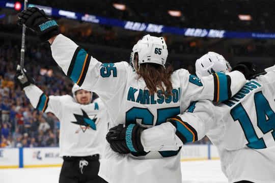 San Jose Sharks defenseman Erik Karlsson (65) celebrates with Gustav Nyquist (14) and Logan Couture, left, after Karlsson scored the winning goal against the St. Louis Blues during overtime in Game 3.