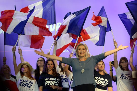 Far-right National Front president Marine Le Pen, waves to supporters during a meeting in Frejus, southern France.