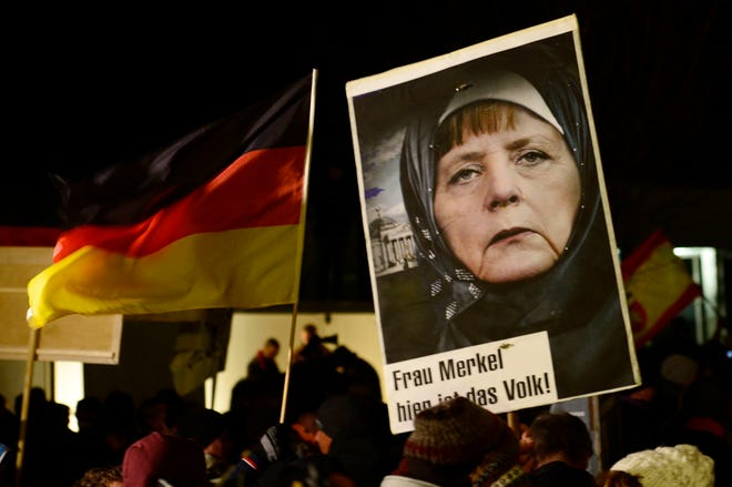 """In this Jan. 12, 2015 file photo, a protestor holds a poster with a manipulated image of German Chancellor Angela Merkel wearing a headscarf and the Reichstag with a crescent on top, during a rally by the group Patriotic Europeans Against the Islamization of the West (PEGIDA) in Dresden, Germany. Words on poster read, """"Mrs. Merkel, here is the people."""""""