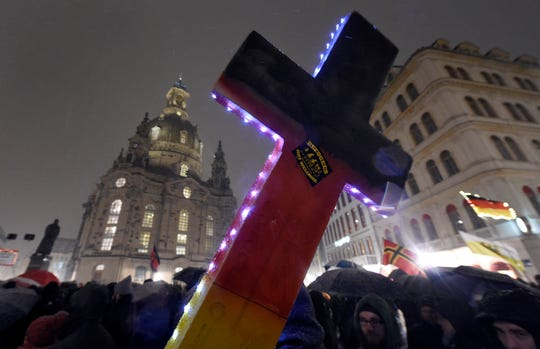 """In this Monday, Feb. 29, 2016 file photo, an illuminated cross with a sticker reading """"Refugees not welcome"""" is displayed during a demonstration by PEGIDA (Patriotic Europeans against the Islamization of the West), near the Frauenkirche church in Dresden, eastern Germany."""
