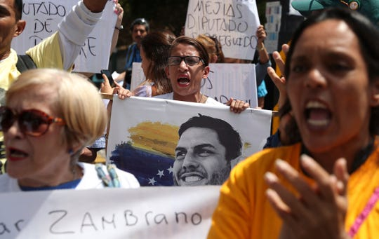 A woman holds an image of jailed opposition lawmaker and outspoken critic of President Nicolas Maduro, Juan Requesens, as she chants with others in support of the opposition controlled National Assembly, in Caracas, Venezuela, Thursday, May 16, 2019.