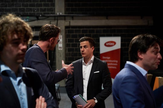 In this April 23, 2019 photo, Vlaams Belang party candidate Dries van Langenhove speaks with attendees at a debate with other party leaders in Zemst, Belgium.