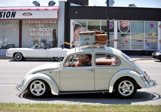 A couple cruises in a 1966 Volkswagen Beetle during the 2015 Woodward Avenue Dream Cruise near  9 Mile  in Ferndale.