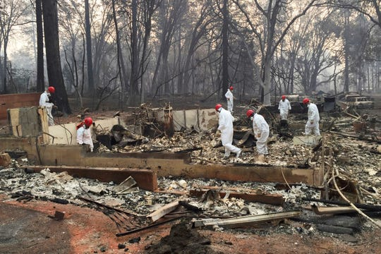 In this Nov. 15, 2018 file photo, volunteer rescue workers search for human remains in the rubble of homes burned in the Camp Fire in Paradise, Calif.