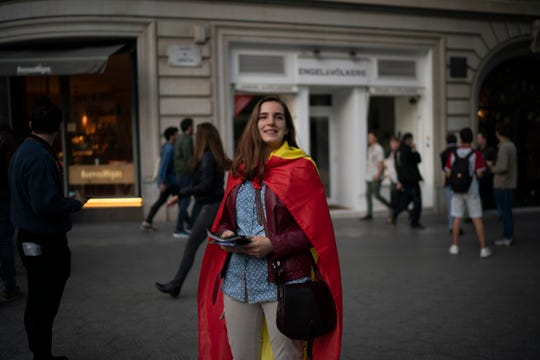 In this May 11, 2019 photo, far-right Vox supporter Amanda Puiggros, 22, distributes flyers after a party meeting in Barcelona, Spain.