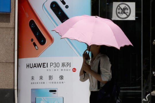 A woman walks past advertisement for Huawei smartphones in Beijing on Thursday, May 16, 2019.