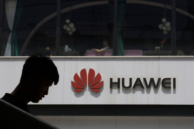 A Chinese man is silhouetted near the Huawei logo in Beijing on Thursday, May 16, 2019.