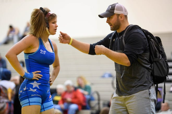Matt Coughlin, right, coaches Kaylie during her exhibition match against Ciera Broukal, not pictured, following the Indiana State Wrestling Association Women's Freestyle State tournament at Avon High School in Avon, Ind., Sunday morning, May 5, 2019. Kaylie was automatically named the Schoolgirl 127-pound state champion due to a lack of opponents so an exhibition match was arranged for her to gain more practice.