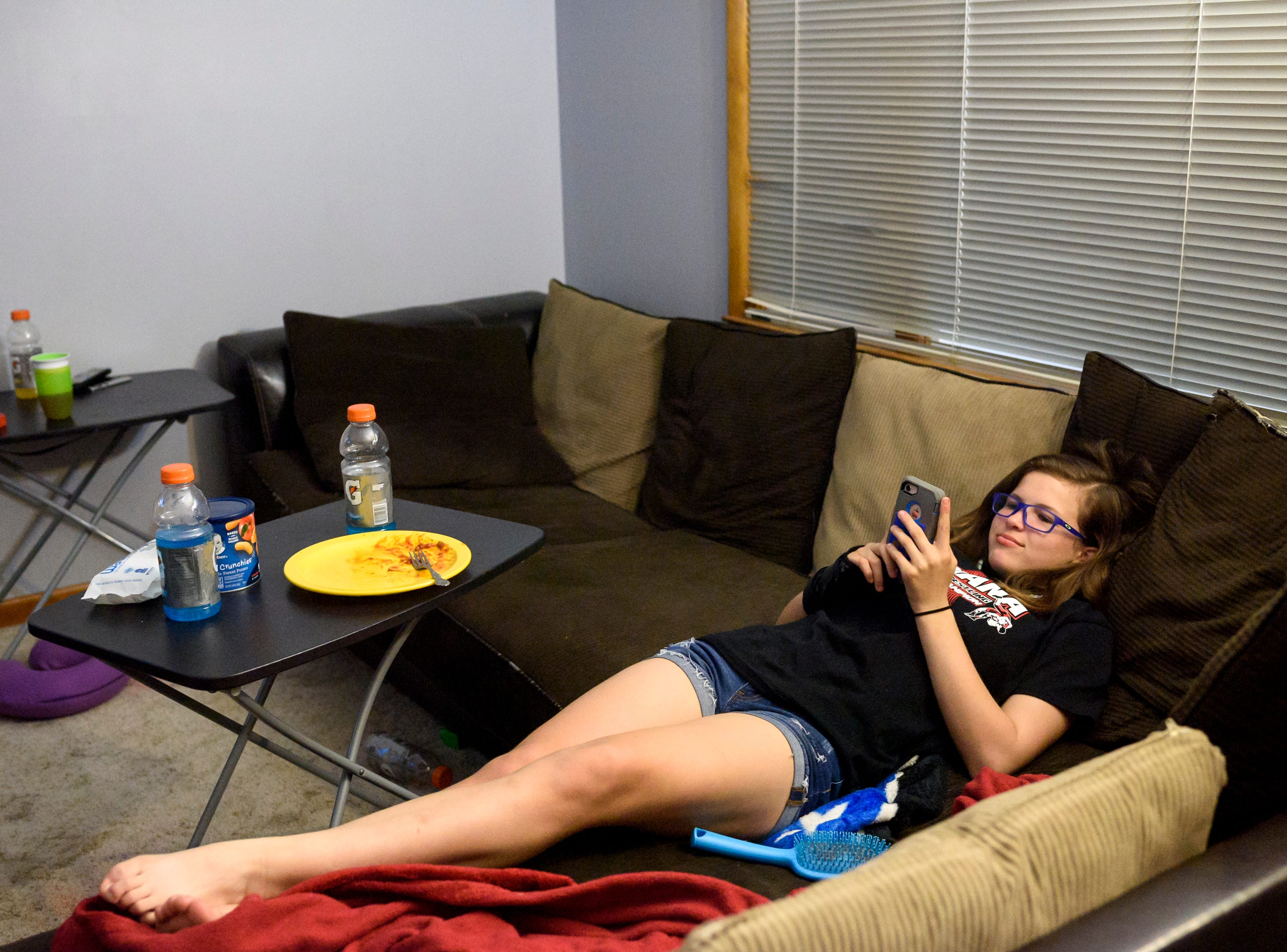 Kaylie takes a moment to relax on the couch after finishing a spaghetti dinner and before breaking out her homework, Tuesday evening, May 14, 2019. Throughout the week Kaylie juggles schoolwork with travel soccer and wrestling leaving Fridays as her only free days to relax and be a typical teenager.