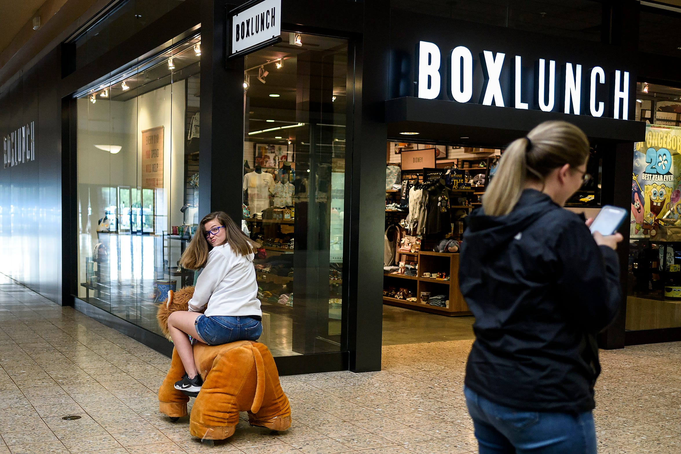 Before shopping for an eighth grade graduation outfit, Kaylie Petersen, left, makes her mother Rachel Petersen, right, laugh while riding around Eastland Mall on a motorized lion, Tuesday evening, May 14, 2019. Kaylie doesn't like wearing dresses so they found a black jumpsuit and a cardigan for her to wear.