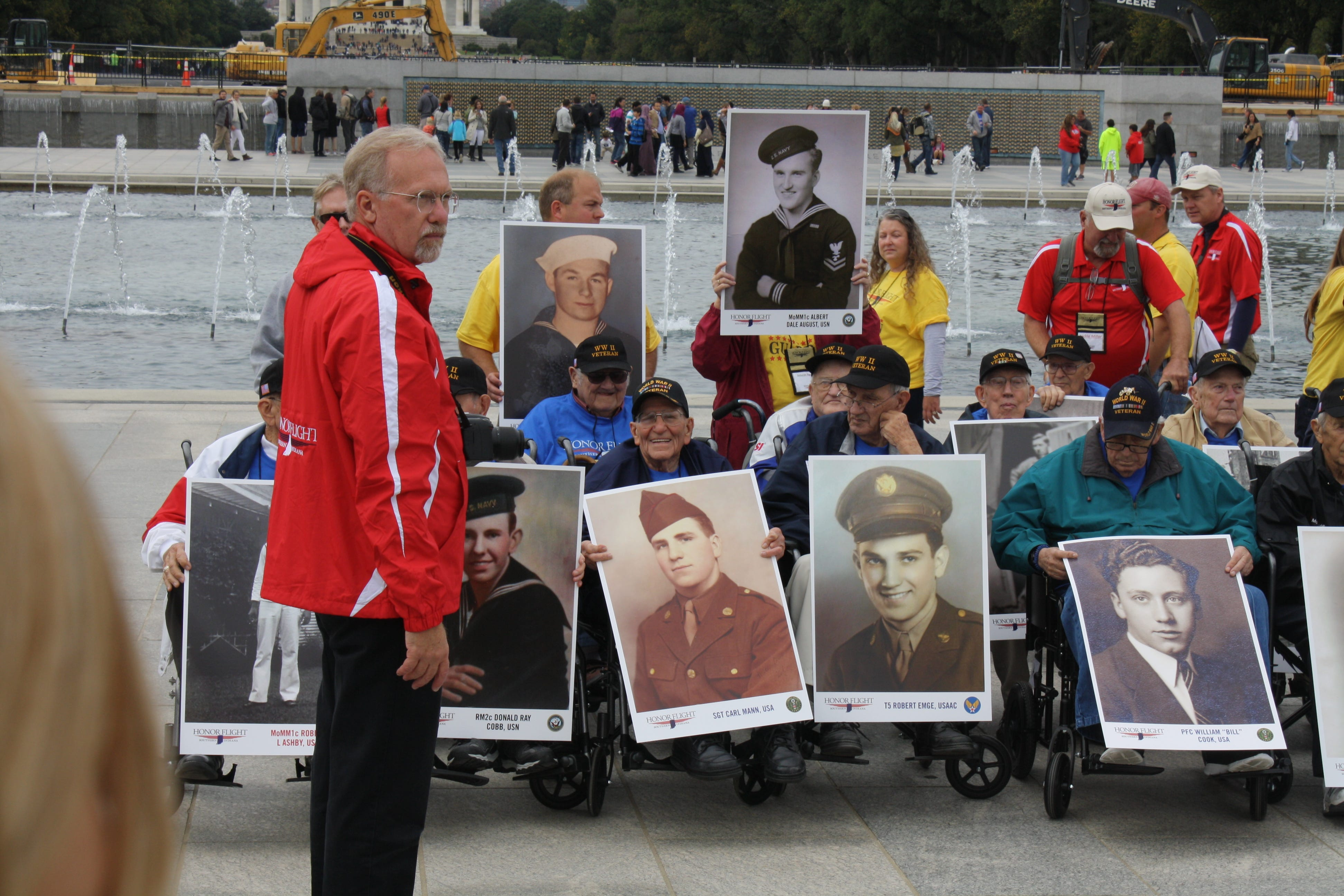 Carl Mann sits at the WWII Memorial with the rest of his Honor Flight Class.