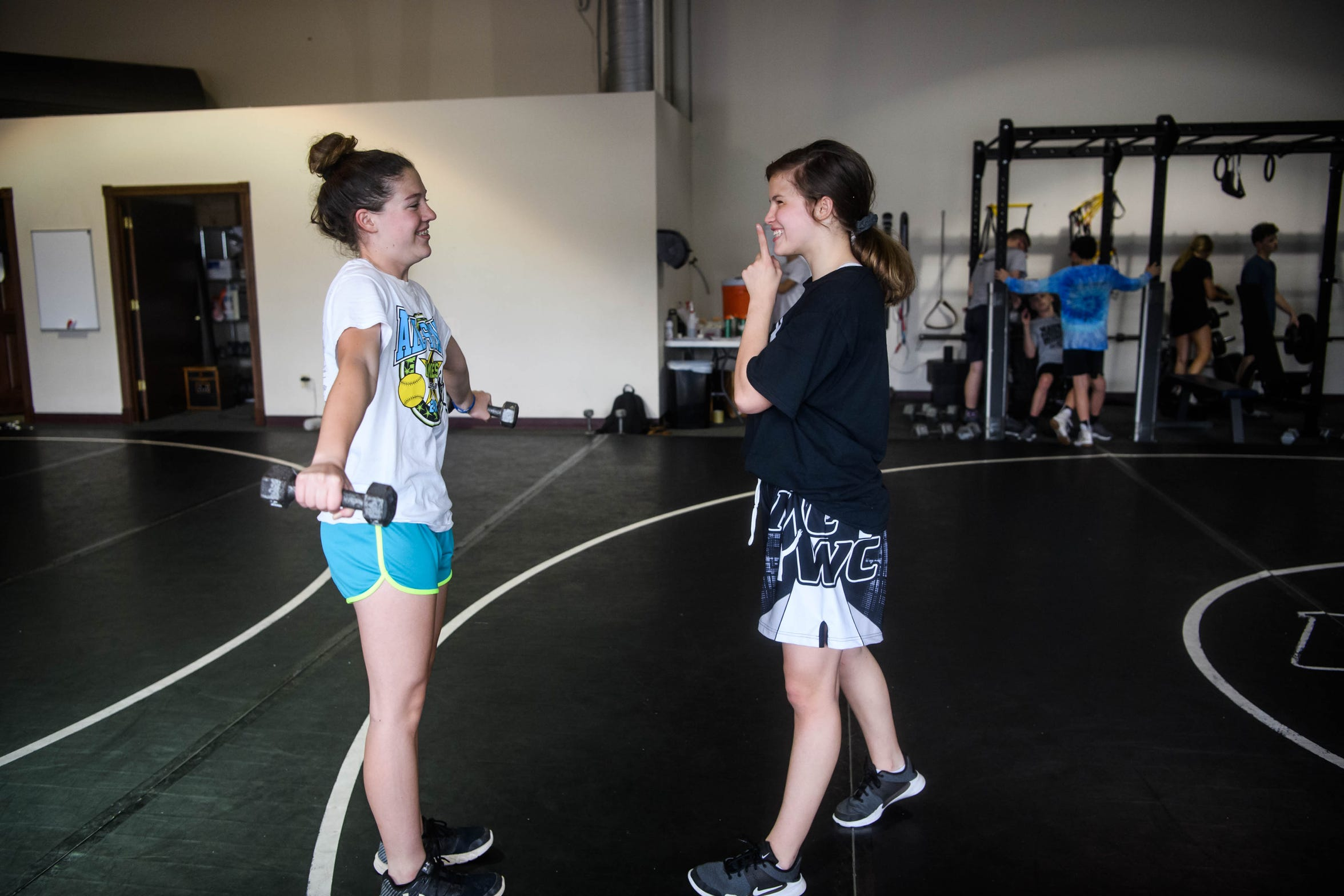 Kaylie jokingly shushes her friend Jacie Arnold, left, as they tease each other during a weightlifting session at Maurer Coughlin Wrestling Club in Evansville, Ind., Thursday, May 2, 2019. Arnold is a softball player who started weightlifting alongside Kaylie and other wrestlers to stay in shape.