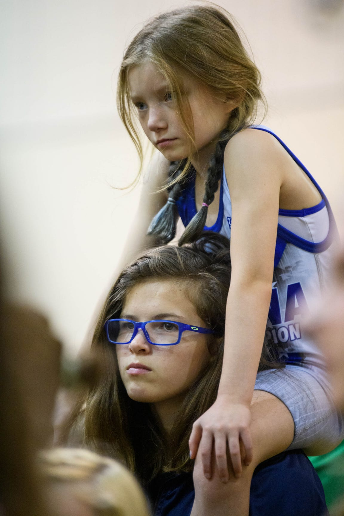Eight-year-old Gloria Cloud and Kaylie listen to an opening speech from Jason DeLois, president of Indiana Girls Wrestling, before the start of the Indiana State Wrestling Association Women's Freestyle State tournament at Avon High School in Avon, Ind., Sunday morning, May 5, 2019. There were 257 high school girls wrestlers in Indiana last season, according to DeLois.
