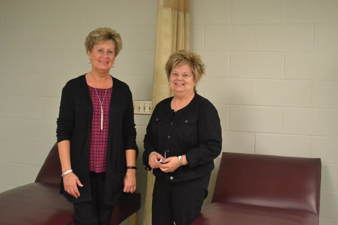 Janet Wendt, Woodmore's Director of Health Services, on left, and LuAnne Juergens, Food Service Director, stand next to the couches in Wendt's office where countless numbers of students have rested under her care. Both women will be retiring at the end of the school year after three decades with the district.