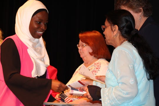 Abibat Omolola Oguntade-Alabi, of Nigeria is welcomed with handshakes as an American Citizen Thursday during a Naturalization ceremony held at Gibsonburg High School.