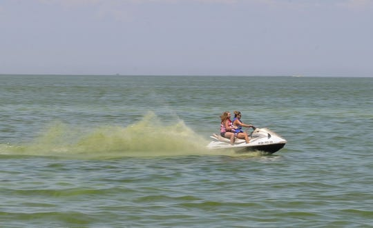 Jet skiers churn up toxic blue-green algae on Lake Erie in Port Clinton in the summer of 2015. There could be a more severe algal bloom on Lake Erie this year than 2018.