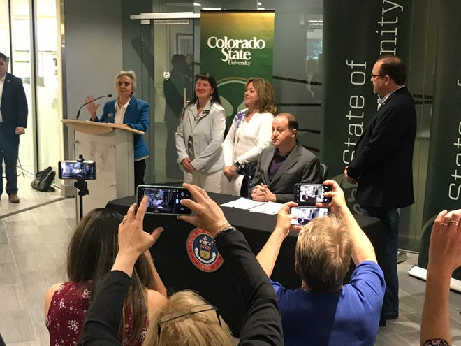State Sen. Joann Ginal, D-Fort Collins, left, speaks before Gov. Jared Polis, seated, signs her bill requiring the state to develop a program to import cheaper, but identical, prescription medication from Canada.