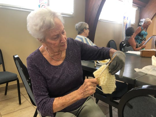 Helen Crombe knits a chemo cap during a meeting of the Southwest Florida chapter of the Embroiderers' Guild of America.  The caps are donated to local hospitals for patients to use.