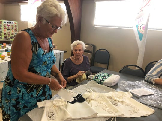 Betty Kingsnorth adjusts one of the dresses she made to donate to the hospital for babies that die soon after birth.