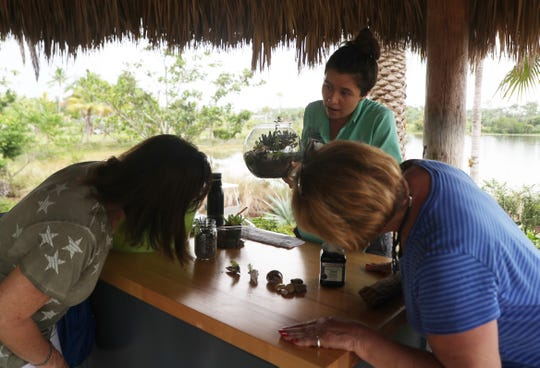 Donnamarie Richmond, an education programs assistant at Naples Botanical Garden teaches Dina May of St. Petersburg and Linda Sullivan how to make a terrarium.